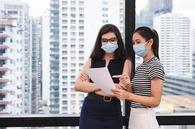 Colega asiática segurando a papelada, consultoria com gerente caucasiano no escritório. usando máscara facial de proteção contra pandemia de coronavírus, covid-19