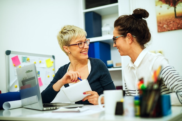 Colega de duas belas mulheres de meia idade trabalhando juntos e olhando uns aos outros enquanto está sentado na mesa no escritório.