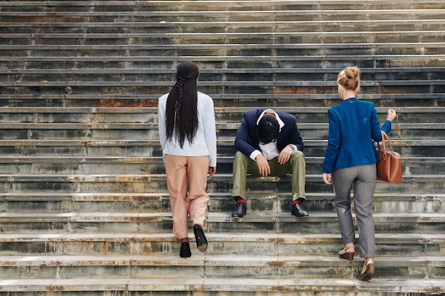 Colega de trabalho estressada sentada nos degraus
