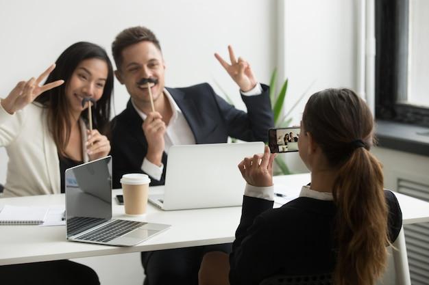 Colega de trabalho tirando foto no smartphone de colegas com bigode falso