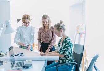 Colega do sexo feminino discutir projeto de negócios no local de trabalho no escritório