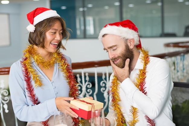Colegas alegres em chapéus de natal trocando presentes
