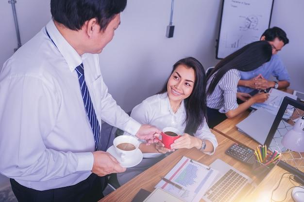 Colegas alegres que compartilham e que apreciam o café junto no escritório.