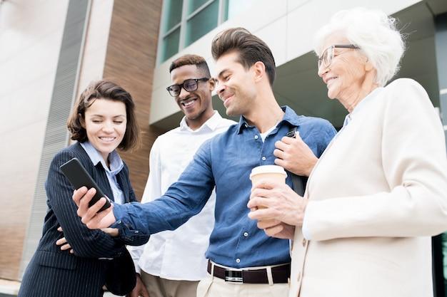 Colegas alegres, usando o aplicativo móvel conveniente para negócios