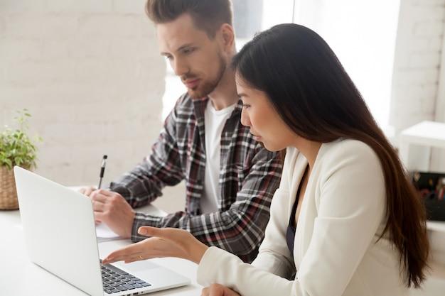 Colegas asiáticos e caucasianos trabalhando juntos discutindo tarefa com laptop