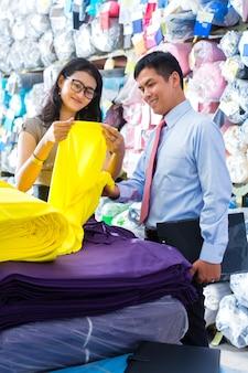 Colegas asiáticos em um armazém, escolhendo panos