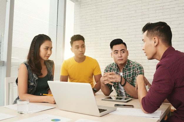 Colegas asiáticos jovens vestidos casualmente de brainstorming juntos no escritório