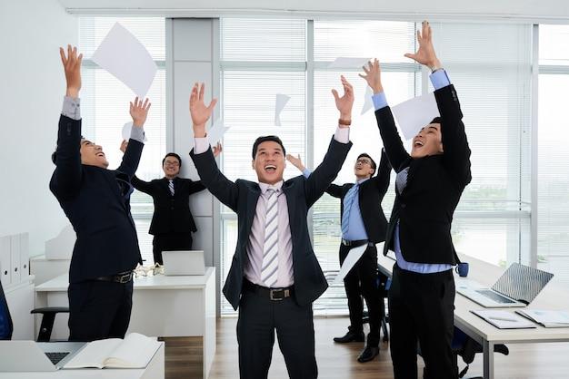 Colegas asiáticos que comemoram o sucesso