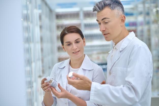 Colegas. atento para discutir mulheres adultas e homens de jaleco branco com medicamentos nas mãos, em pé na farmácia