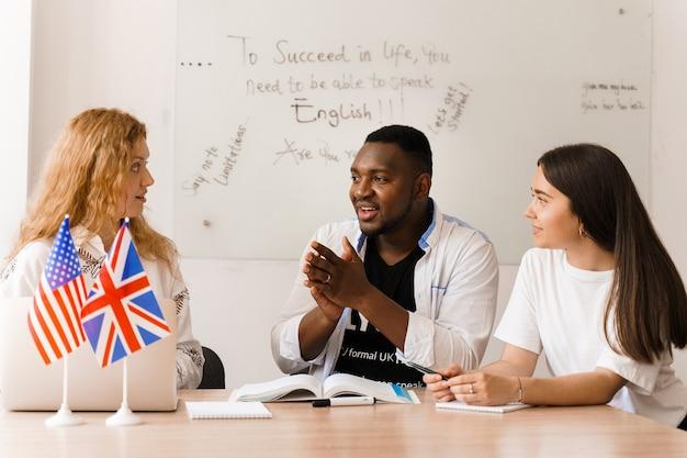 Colegas atraentes e amigáveis trabalhando juntos em um escritório, discutindo algo na sala branca