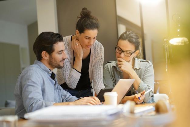 Colegas atraentes, olhando por cima de idéias no espaço de trabalho de co