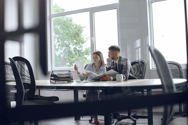Colegas bebem café. parceiros de negócios em uma reunião de negócios. homem e mulher sentados à mesa