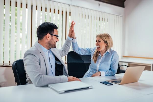 Colegas bem sucedidos do negócio que dão a elevação cinco no escritório.