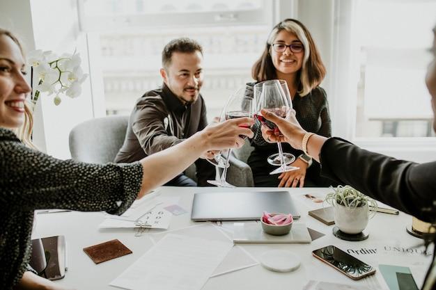Colegas brindando taças de vinho no trabalho
