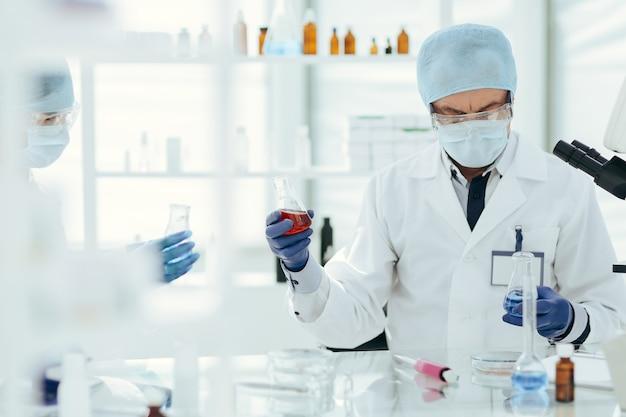 Colegas cientistas verificando o líquido em frascos de laboratório