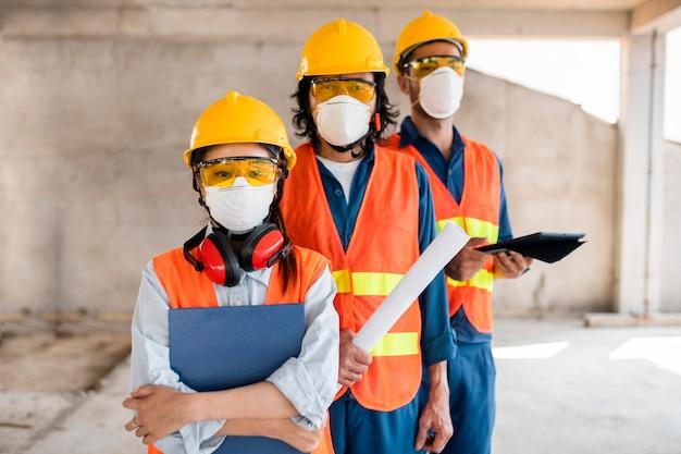 Colegas com equipamentos de segurança trabalhando com plantas