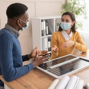 Colegas com máscaras trabalhando juntos no projeto de meio ambiente