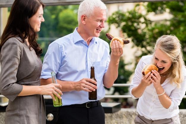 Colegas comendo salsichas e cerveja depois do trabalho