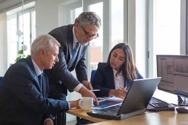 Colegas concentrados observando gráficos estatísticos e conversando sobre o trabalho. gerentes seniores profissionais e jovem assistente preparando o plano de negócios. conceito de trabalho em equipe, gestão e parceria