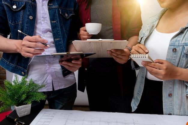 Colegas da equipe discutindo dados de trabalho e tablet, laptop com projeto arquitetônico no canteiro de obras na mesa no escritório cores quentes luz do sol