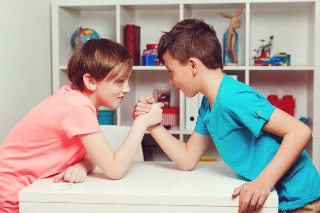 Colegas de classe competindo em queda de braço durante o intervalo. amigos felizes jogando queda de braço, olhando um para o outro.
