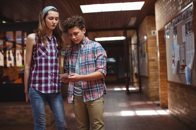 Colegas de classe usando telefone celular no corredor da escola