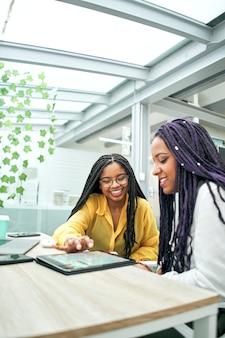 Colegas de empresária felizes em um escritório moderno usando o tablet