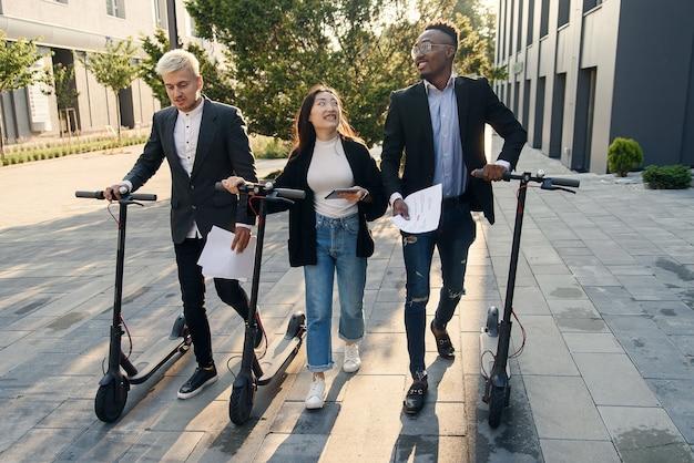 Colegas de escritório multirraciais felizes e confiantes discutindo projeto de negócios vão perto do prédio de escritórios com scooters elétricas