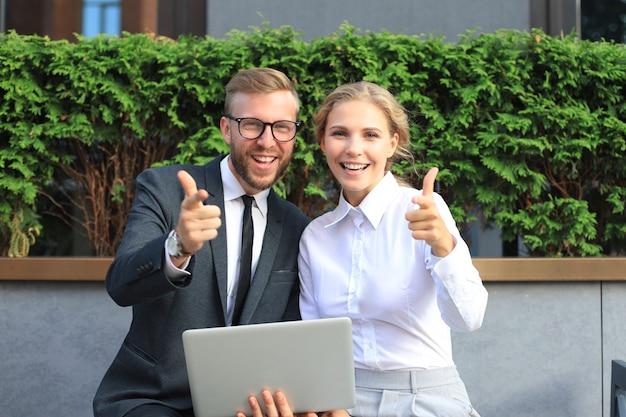 Colegas de escritório usando laptop e mostrando os polegares enquanto está sentado em um banco ao ar livre.