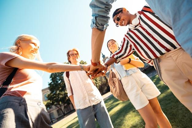 Colegas de grupo felizes juntando as mãos