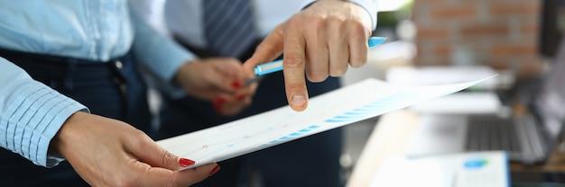 Colegas de homem e mulher examinam o documento com a programação no local de trabalho, em close-up do escritório da empresa. conduzindo o conceito de treinamentos de negócios.