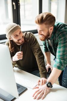 Colegas de homens felizes no escritório usando o computador. olhando de lado.