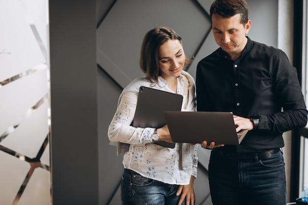 Colegas de mulher de negócios e homem de negócios, trabalhando no laptop