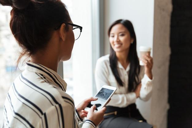Colegas de mulheres falando entre si