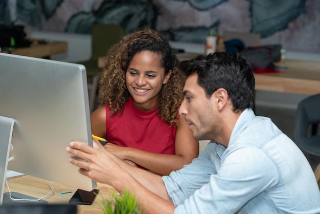 Colegas de negócios criativos jovens discutindo novo projeto de inicialização no escritório local de trabalho