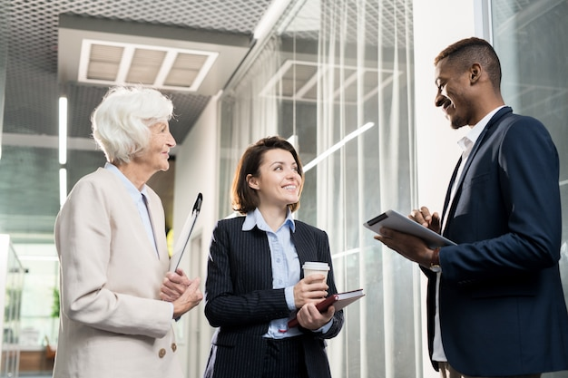 Colegas de negócios positivos discutindo o desenvolvimento da empresa