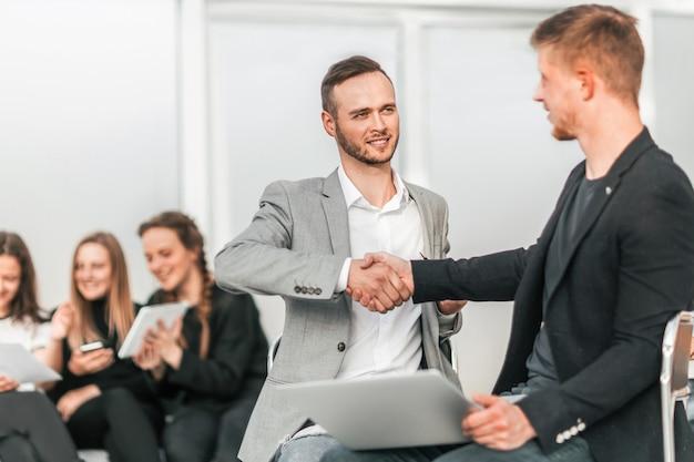 Colegas de negócios sérios apertando as mãos uns dos outros