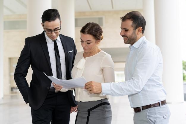 Colegas de trabalho a checar documentos de negócios em reunião a sorrir