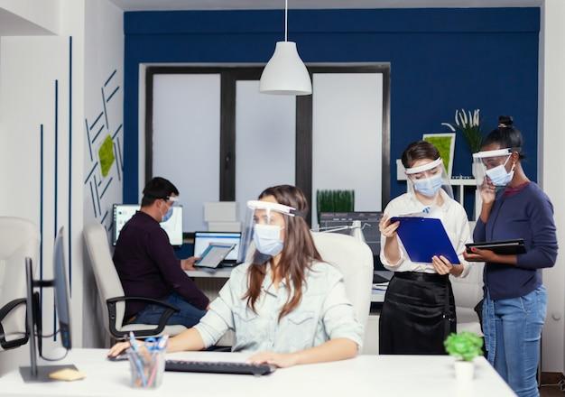 Colegas de trabalho africanos e caucasianos cooperando no local de trabalho usando máscara contra covid19. equipe de negócios multiétnica trabalhando respeitando a distância social durante a pandemia global de coronavírus.