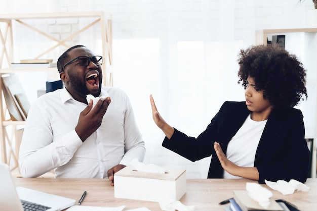 Colegas de trabalho africanos sentado à mesa com homem espirros.