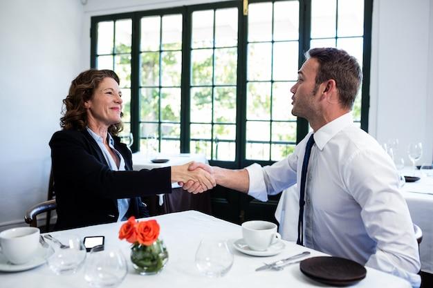 Colegas de trabalho, apertando as mãos após uma reunião bem sucedida
