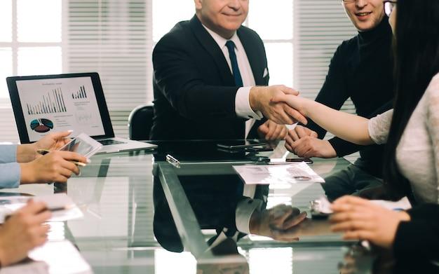 Colegas de trabalho apertando as mãos durante uma reunião de trabalho. o conceito de trabalho em equipe