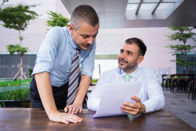 Colegas de trabalho bem sucedido alegre discutindo documentos