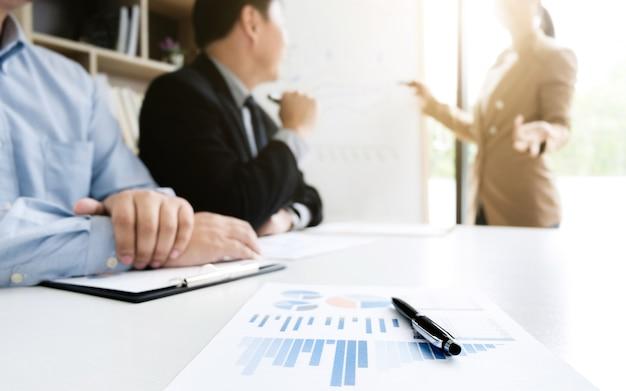 Colegas de trabalho brainstorming discutindo o desempenho da venda no quadro branco durante a apresentação na sala de escritório moderna, foco seletivo