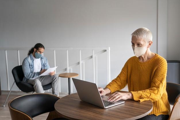 Colegas de trabalho com máscaras médicas trabalhando