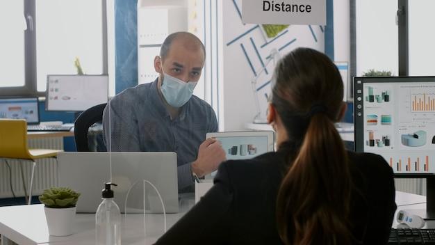 Colegas de trabalho com máscaras protetoras falando sobre estatísticas de gerenciamento usando um computador tablet sentado no novo escritório normal da empresa. equipe mantém distanciamento social para evitar infecção por coronavírus