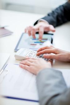 Colegas de trabalho, comparando estatísticas de negócios