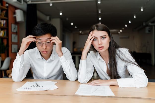 Colegas de trabalho concentrados e cansados no escritório