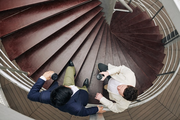 Colegas de trabalho conversando na escada em espiral