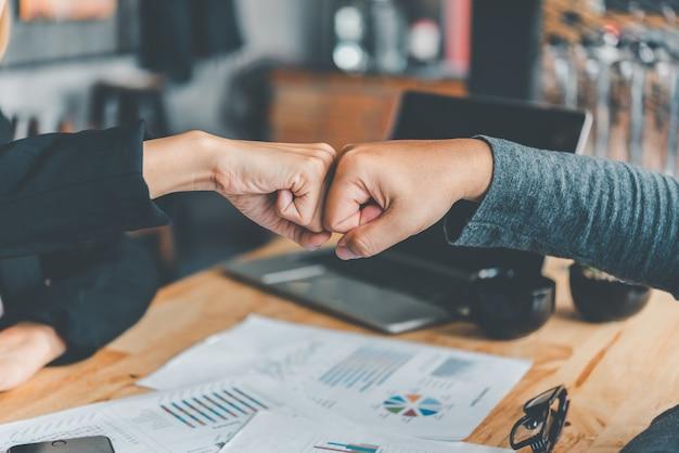 Colegas de trabalho dando um soco no punho ficam felizes em trabalhar juntos com sucesso, trabalhando em uma equipe confiável